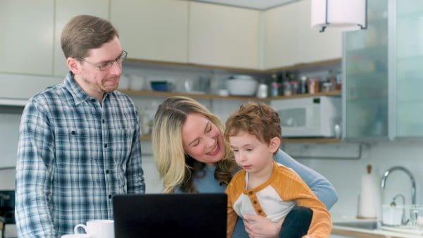 Family in kitchen with their laptop talking to their pediatrician over a telehealth platform